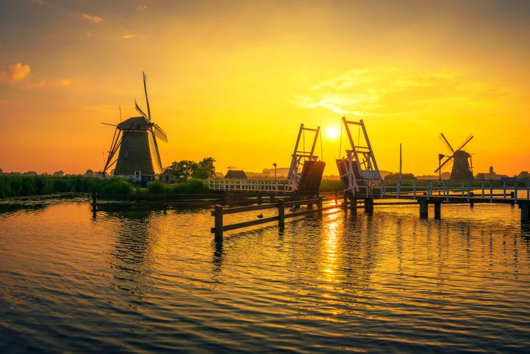 Beautiful sunset above a historic wooden drawbridge and old windmills in Kinderdijk, Netherlands. This system of 19 windmills was built around 1740 and is a UNESCO heritage site.